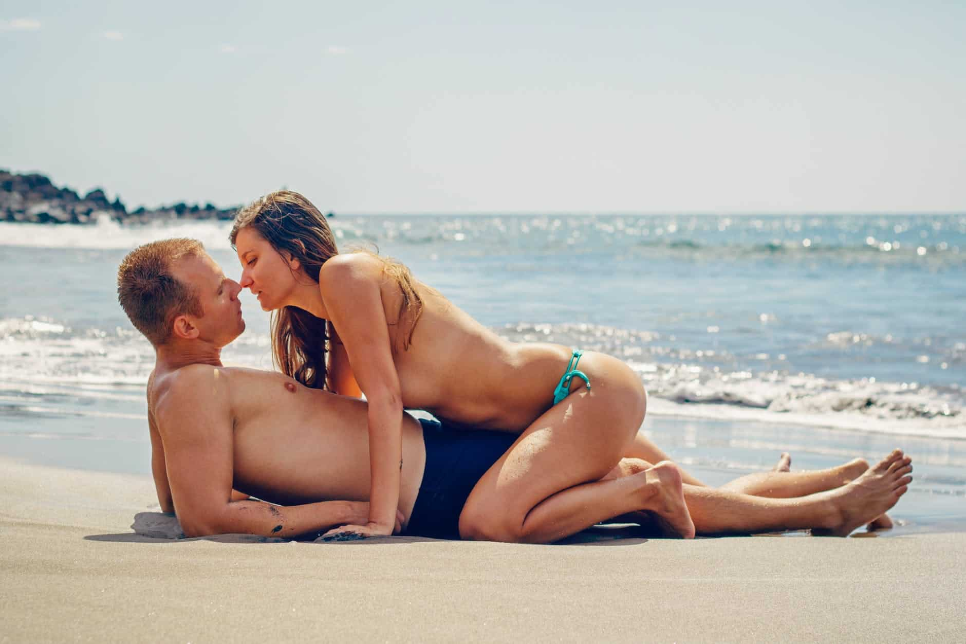 man lying on sand while woman kissing him
